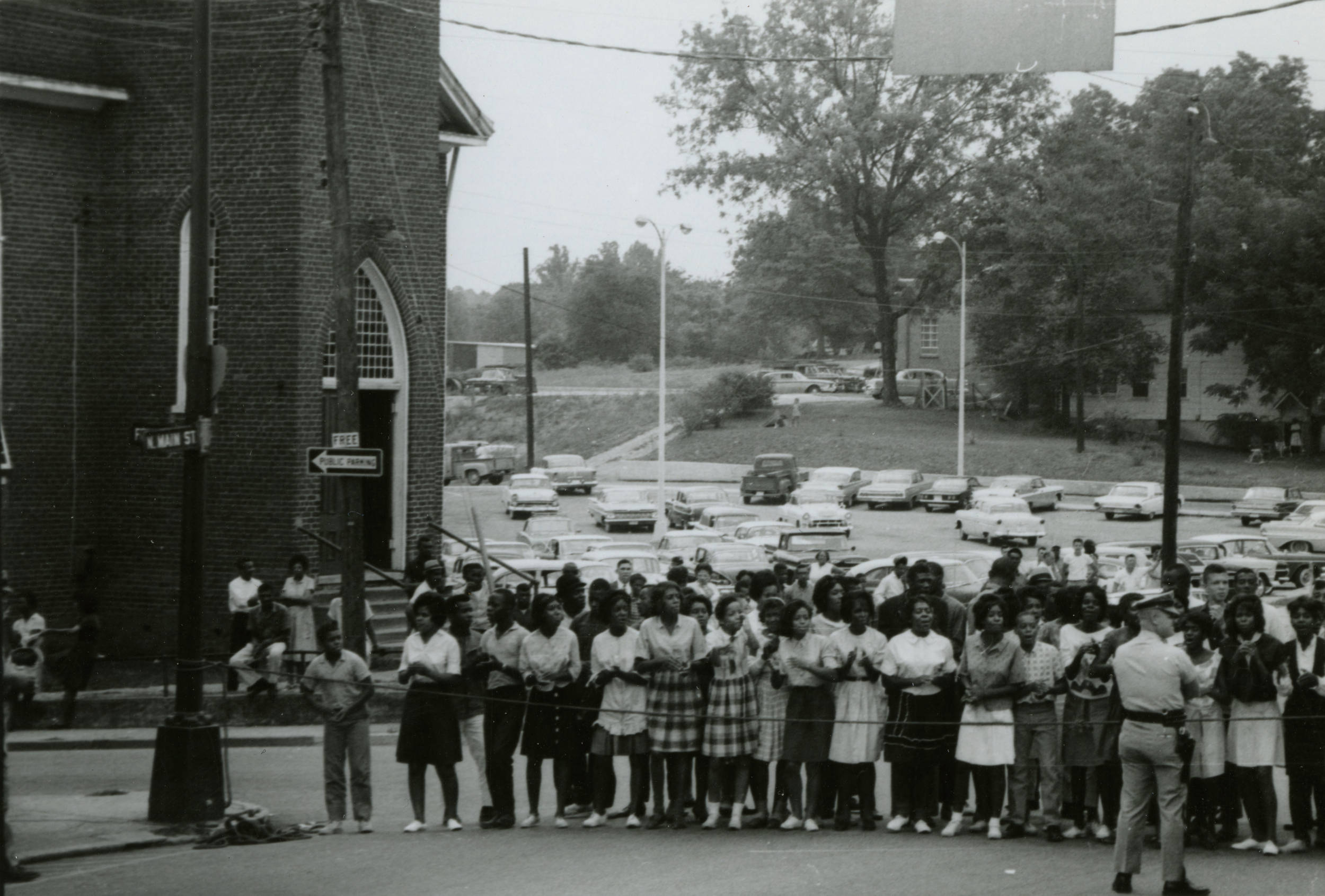 An image of African American students outside of First Baptist Church, with law enforcement officers present