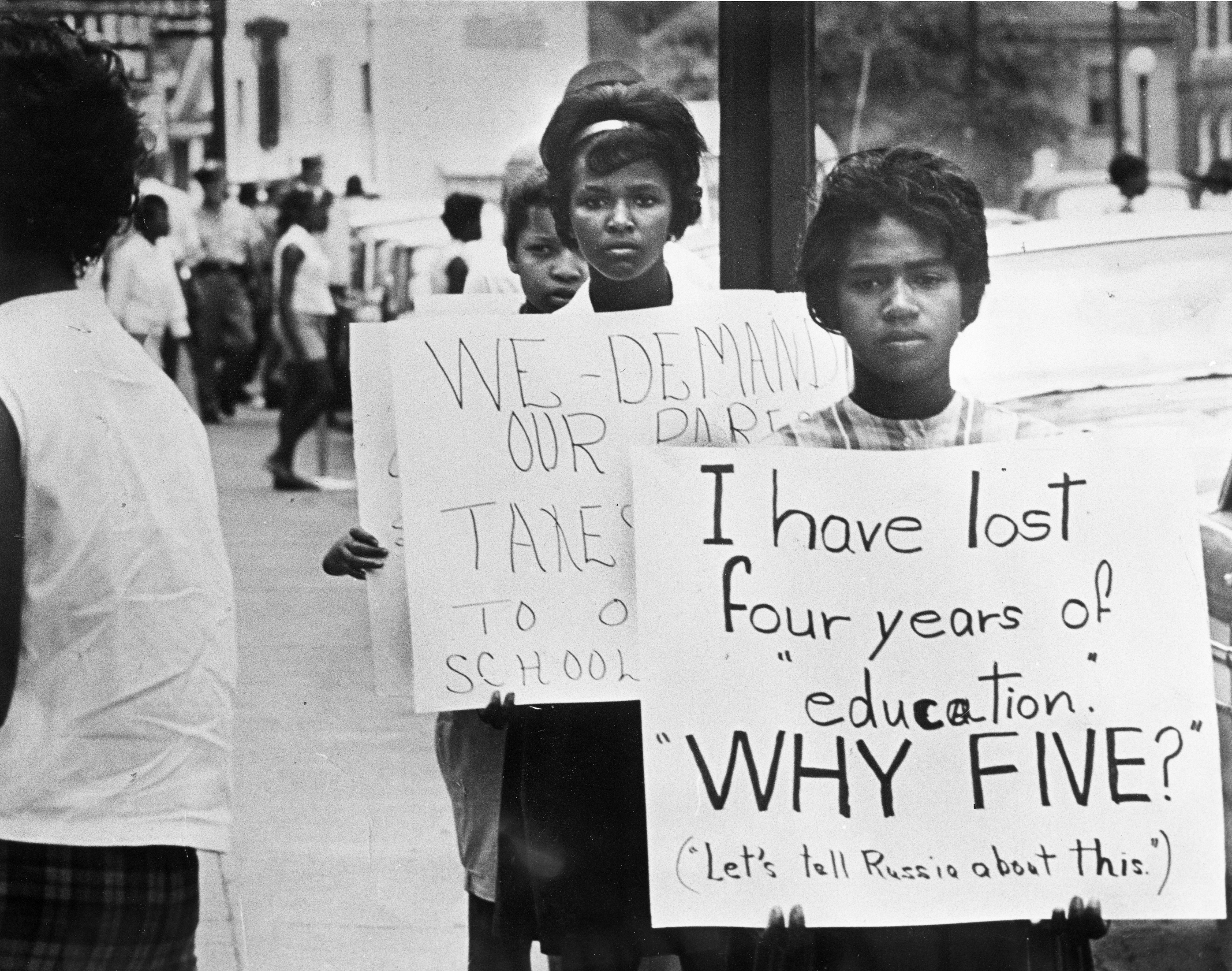 An image of several female African American teenagers holding picket signs